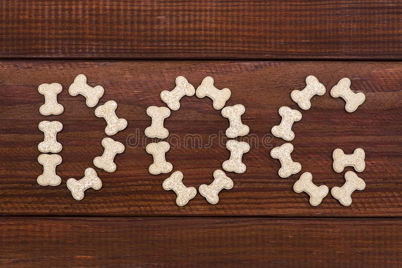Dog bone and dog candy on wood background. Vitamins in the form of bone stock photography