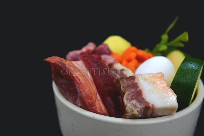 Dog bowl filled with mixture of biologically appropriate raw food containing of meat chunks with fat, egg and healthy vegetables stock image