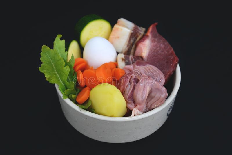 Dog bowl filled with mixture of biologically appropriate raw food containing meat chunks, vegetables, potato, egg stock image