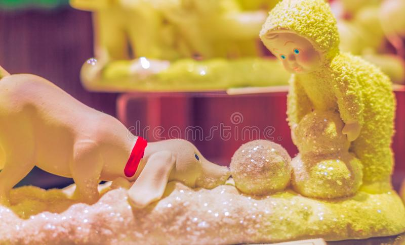Dog and Boy Figurines Building a Snowman royalty free stock photo