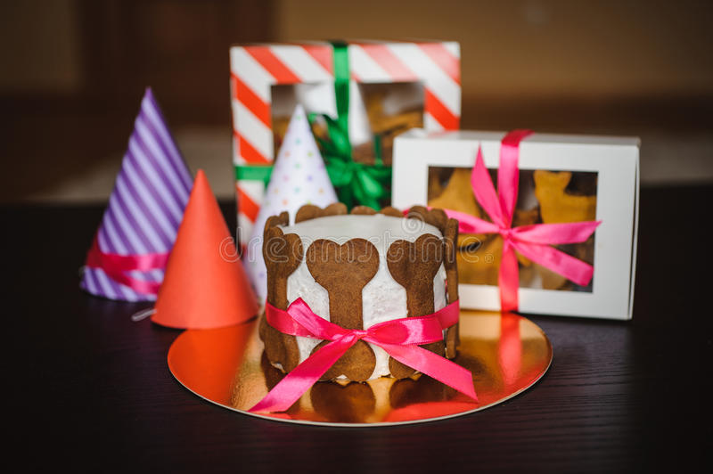 Dog cake and cookie in boxes with birthday hat. Dog cake and cookie in boxes with ribbons and birthday hats royalty free stock images