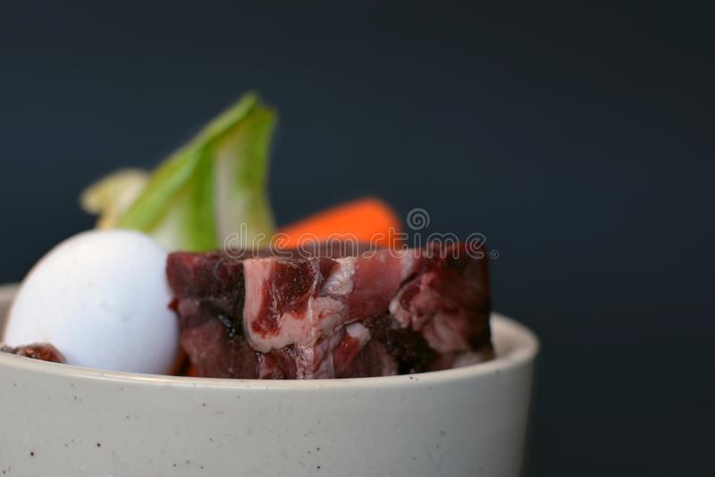 Cat or dog bowl filled with mixture of biologically appropriate raw food containing of meat chunks, egg, entrails and vegetables. Dog or cat bowl filled with royalty free stock images