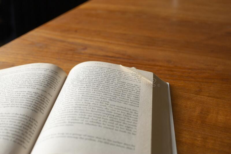 A dog eared page in a paperback on table royalty free stock image