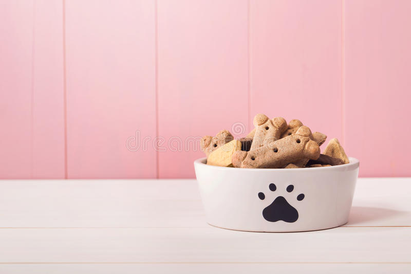 Dog food in a bowl filled with treats. On wooden table stock images