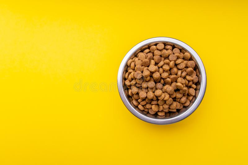 Dog food in a metal bowl. Yellow background royalty free stock images