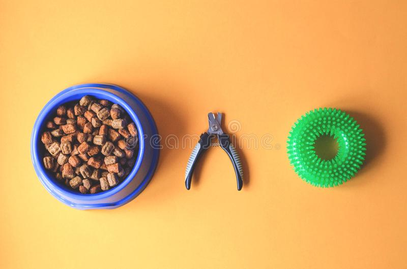 Dog food in a plate with claw scissors and a toy royalty free stock photo