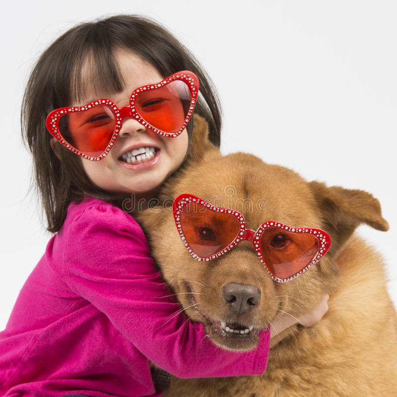 Dog hugged by child. Child giving hug to dog. Both wearing heart shaped shades royalty free stock photo