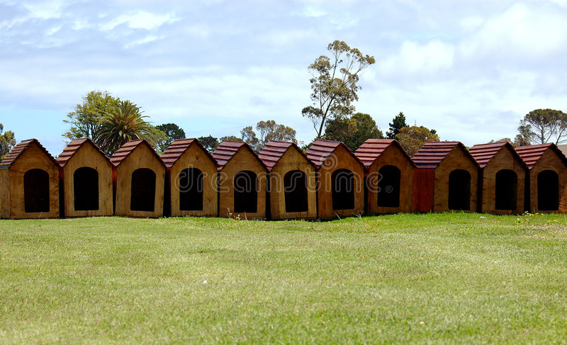 Dog huts. A lot of doggy huts for sale standing in a row outdoors royalty free stock photo