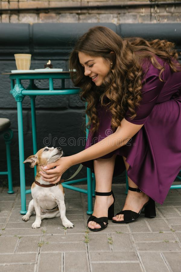 Dog and girl in street cafe. Beautiful woman in purple dress pettin small cute dog sitting under the table. Street cafe stock photos