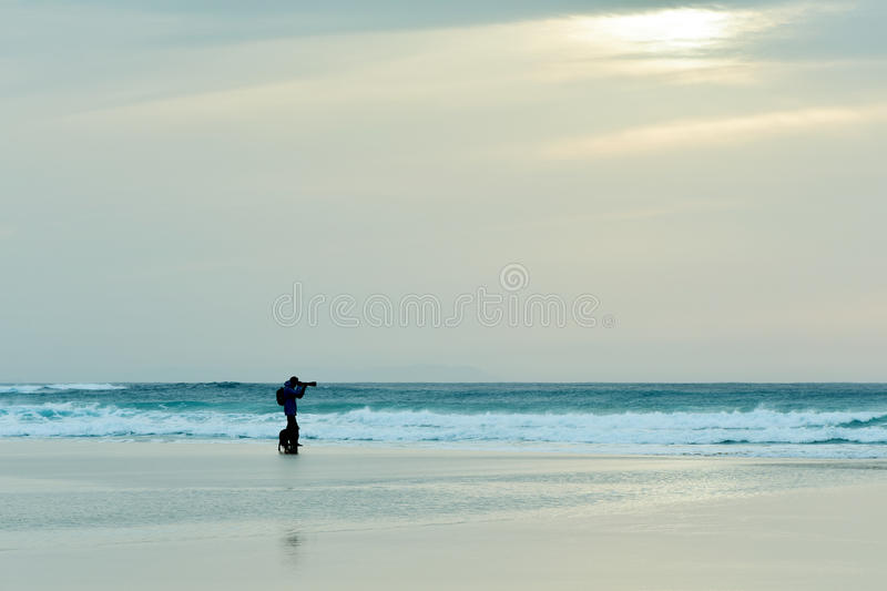 Dog and man taking a picture in front of the sea. The silhouette of a dog and a young caucasian man in the distance taking a picture in front of the sea at royalty free stock photos