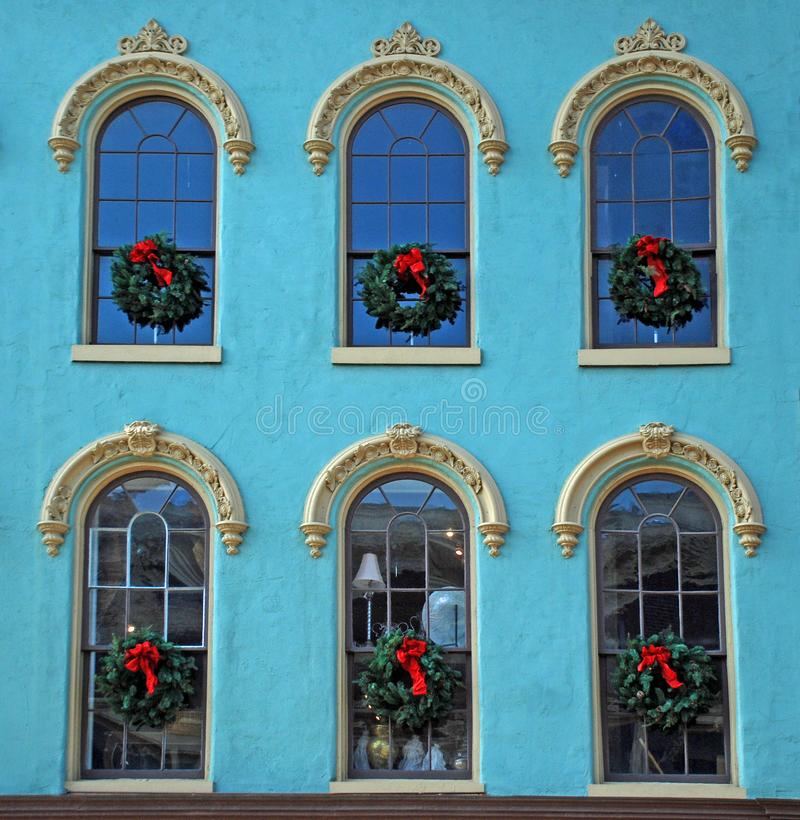 Christmas windows on a blue historic building. Franklin, Tennessee, blue stucco, white molding above windows, Christmas wreaths, red bows, holiday spirit on stock photos