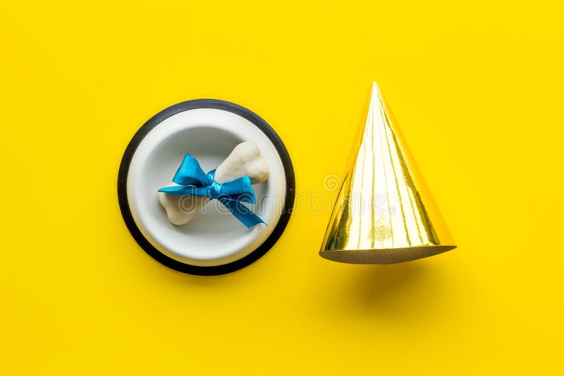 Dog`s birthday concept. Chewing bones with bow and party hat on yellow background top view royalty free stock photos