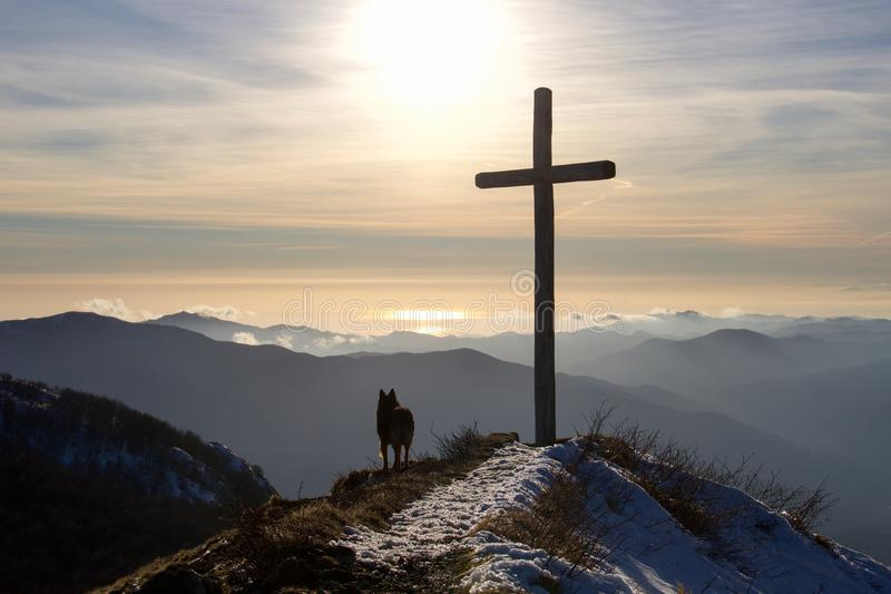 Dog silhouette near a cross on the top of the mountain royalty free stock image