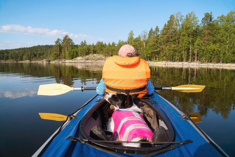 The owner and the dog in a life jacket floating in a kayak boat. Dog sitting in the boat .lake Ladoga.Karelia,Skerries royalty free stock image