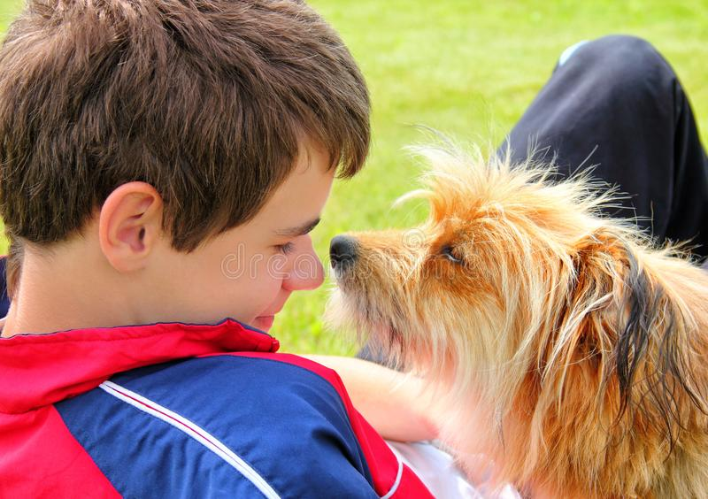 Dog sniffing the boys face. Dog sniffing a boy's face close-up. The concept of friendship and love for animals