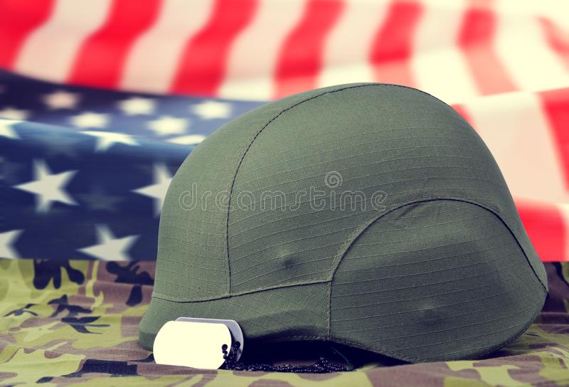 Dog tags and helmet on camouflage fabric in the background American flag. stock photography