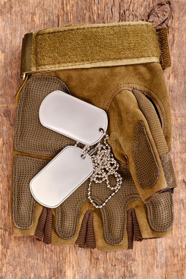 Dog tags on military fingerless glove. Close up, top view. Wooden desk surface background royalty free stock photos