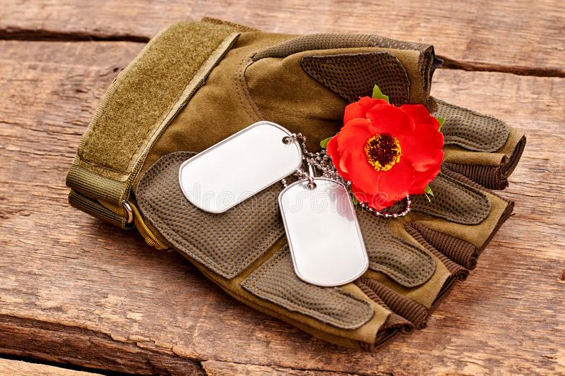 Dog tags and red poppy on military fingerless glove. Wooden desk surface background royalty free stock image