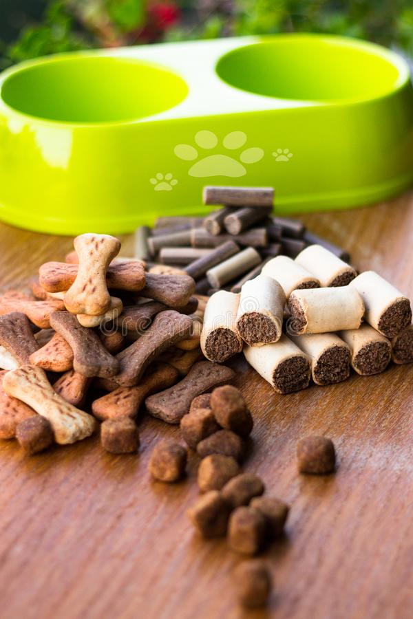 Dog tasty colored biscuits on wooden background, bowl. Dog tasty colored biscuits on wooden background, snacks for dogs. Cracker, crunchy dog biscuit stock image