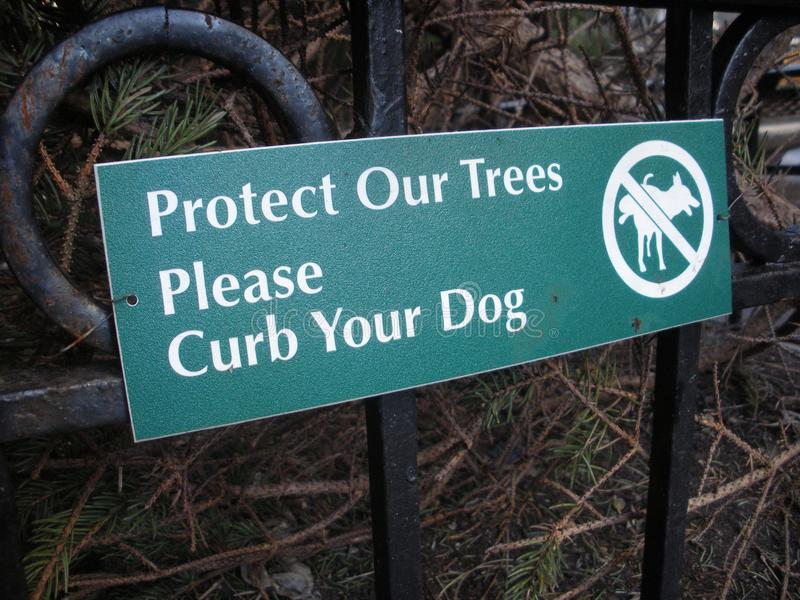 Dog Training, Curb Your Dog Sign. Protect Our Trees, Please Curb Your Dog: Small sign in New York City asking dog owners to respect urban green space. This photo royalty free stock images