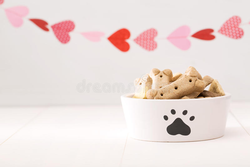 Dog treats on a white bowl. With a garland of hearts stock images