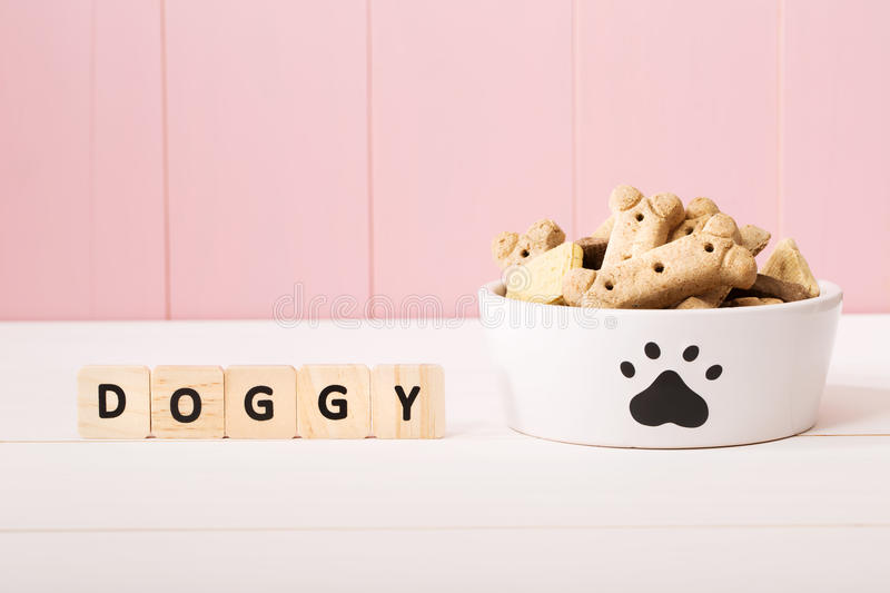 Dog treats on a white bowl. With wood blocks on pink wooden wall royalty free stock images