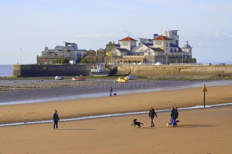 Dog walkers on sand beach. Dog walkers on the beach and Knightstone Island at the resort of Weston super Mare in North Somerset in England stock photography