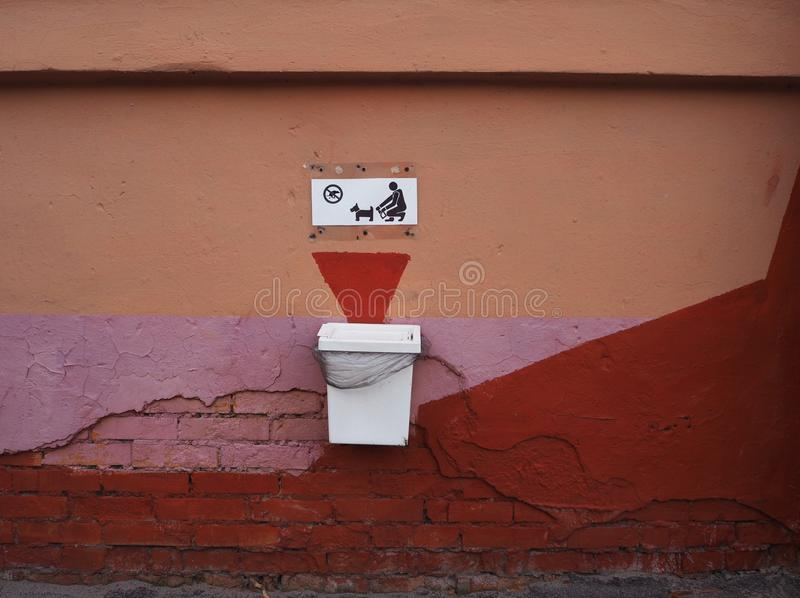 Dog waste basket with a sign saying you must clean up after your dog using dog poop bags stock image