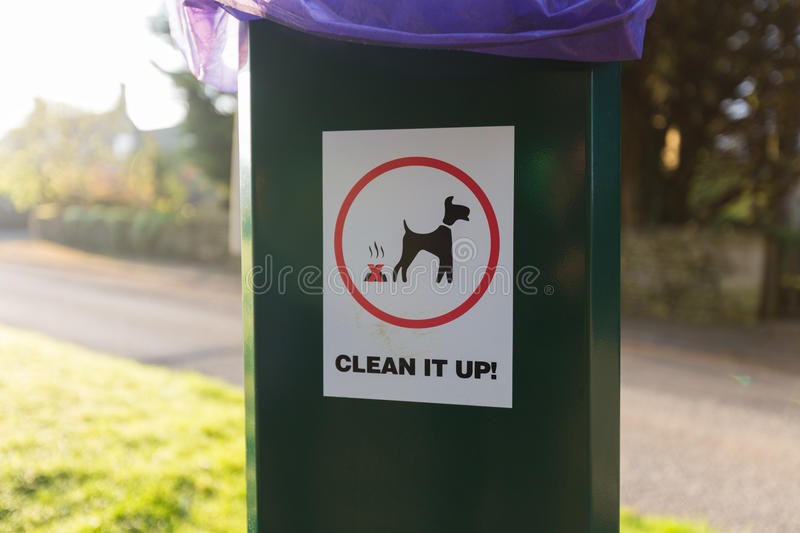 Dog waste clean up sign on plastic trash can royalty free stock image