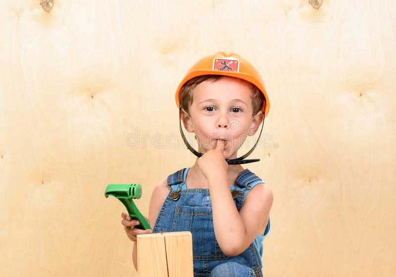 Kid boy as funny builder holding finger in mouth after hitting it with hammer stock photography