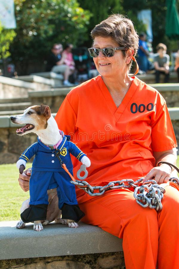 Dog Wearing Prison Guard Costume Is Chained To Female Owner royalty free stock photo