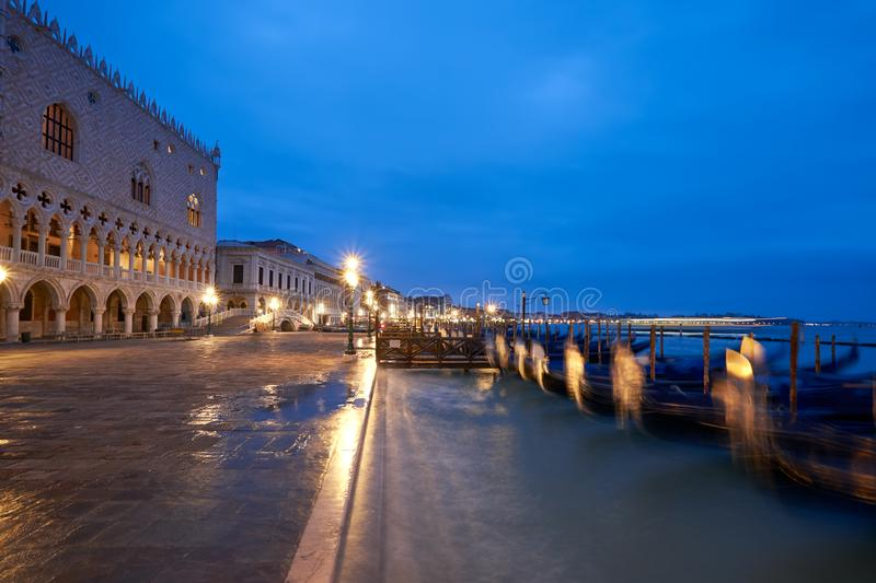 Doge`s Palace, or Doge Palace, and moored gondolas in Venice, It. Doge`s Palace, or Doge Palace, and moored gondolas dancing on waves on a rainy night in Venice stock photos