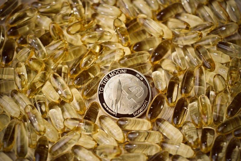 Dogecoin硬币和黄色片剂 库存照片