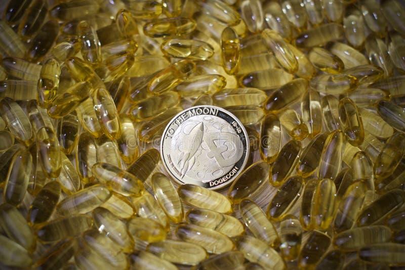 Dogecoin硬币和黄色片剂 库存图片