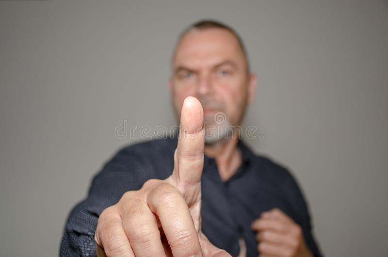 Dogmatic or authoritative man holding up a finger. In a commanding gesture with focus to his hand over a grey studio background stock photo
