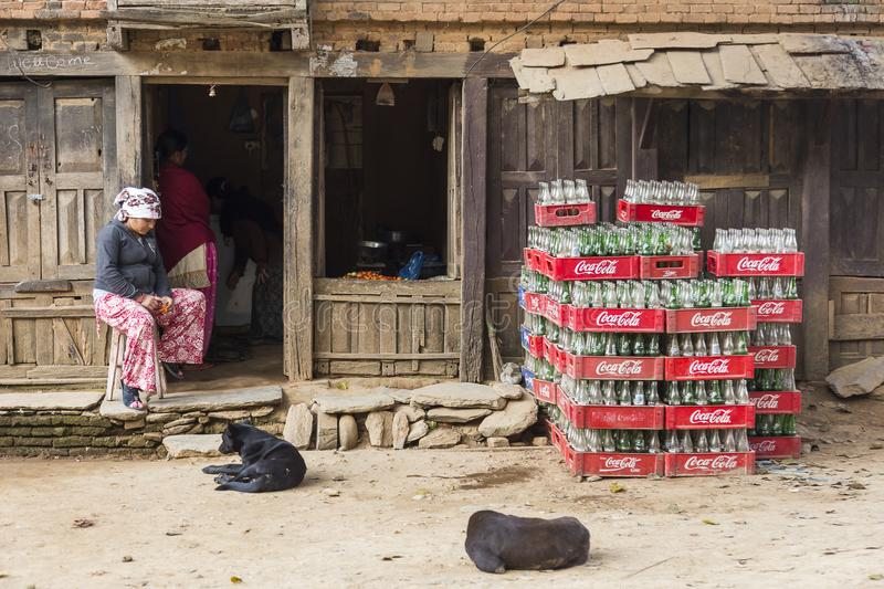 Dogs and woman resting in front of small shop, Bandipur, Nepal stock image