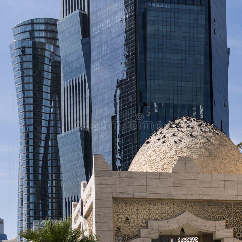 DOHA, CATAR - EM FEVEREIRO DE 2018: Compilação da abóbada da mesquita e de arranha-céus altos azuis modernos na cidade de Doha, C fotografia de stock royalty free
