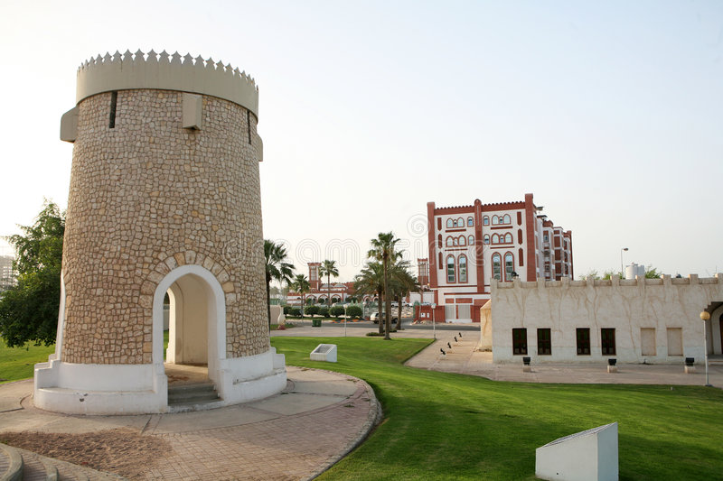 Doha folly. A folly in one of the parks on the Corniche in Doha, Qatar, with arabesque-style restaurants behind stock images