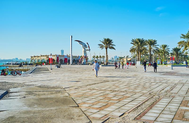 On Doha promenade, Qatar. DOHA, QATAR - FEBRUARY 13, 2018: Seaside Corniche promenade with a view on statue of Olympic Oryx Orry and luxury Balhambar restaurant royalty free stock images