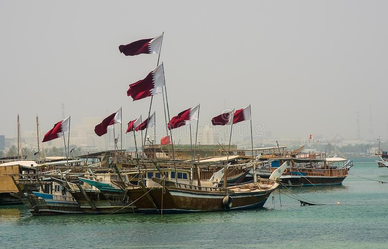 Doha, Qatar Dhows in Port. Near downtown Doha, Qatar, Dhows are moored near the shore. All proudly flying the national flag royalty free stock photo