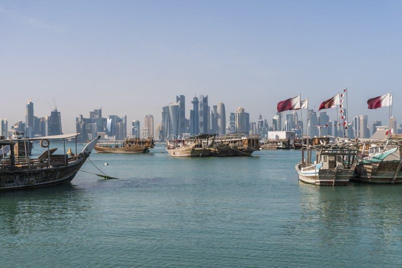 DOHA QATAR - Februari 2018: Härlig Doha horisontsikt med traditionella träfartyg med att sväva qatariska flaggor Corniche royaltyfria bilder