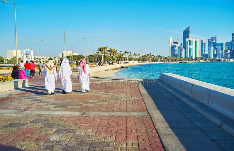 Lazy walk in Doha, Qatar. DOHA, QATAR - FEBRUARY 13, 2018: The Corniche promenade is the best place for the lazy walks, enjoying the seascape and modern stock photo