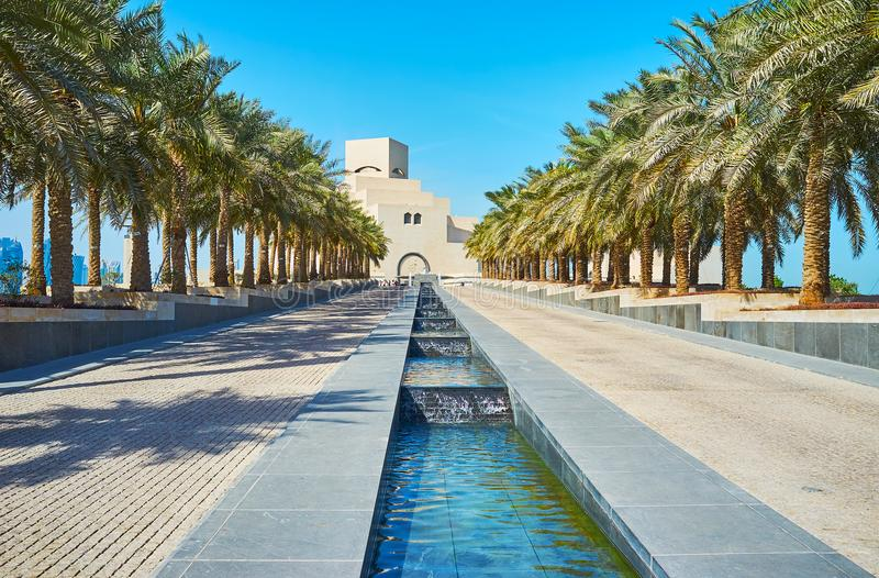 In Museum park of Doha, Qatar. DOHA, QATAR - FEBRUARY 13, 2018: The walk along the rows of palm trees to the Museum of Islamic Art, located at the end of stock photos