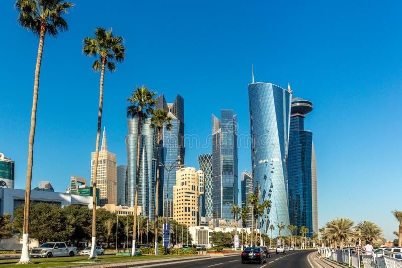 Doha Qatar - Januari 8th 2018 - det moderna centret av den Doha staden med palmträdet, bilar, breda avenyer på en dag för blå him arkivfoton
