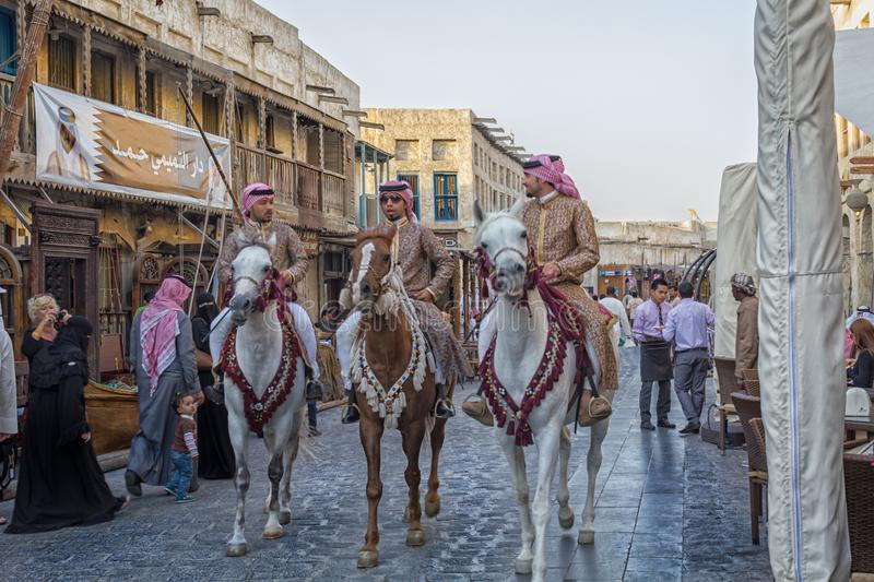 Souk Waqif in Doha Qatar main street day light view with traditional guards riding horses and people. Doha-Qatar, January 24,2013: Souk Waqif in Doha Qatar main stock image
