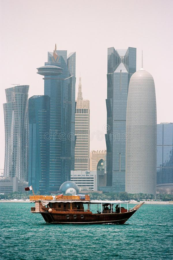 Wooden dhow and Doha Qatar towers. DOHA, QATAR - May 6, 2018: A traditional wooden dhow sails in front of some of Qatar`s skyscrapers in Doha Bay. Film photo royalty free stock photography
