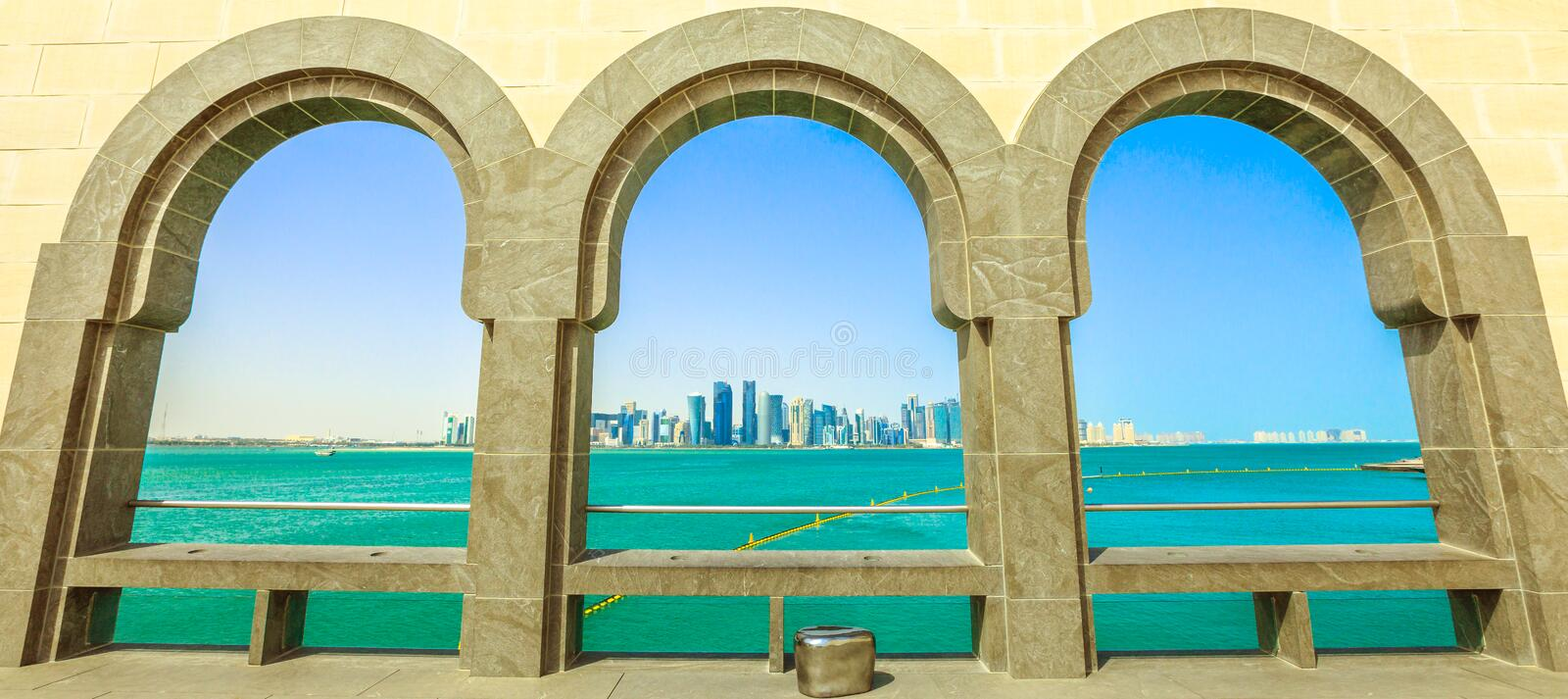 Doha West Bay panorama. Panorama of Doha West Bay skyline through arched windows opening view on Doha Bay. Doha`s waterfront near Corniche. Doha in Qatar royalty free stock photos