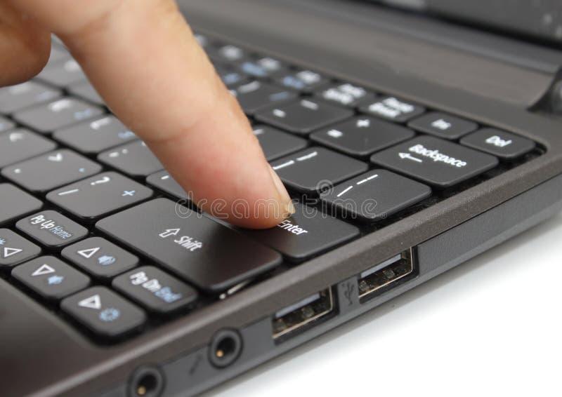 Doigt appuyant sur la touche de pénétrer dans sur un clavier images stock