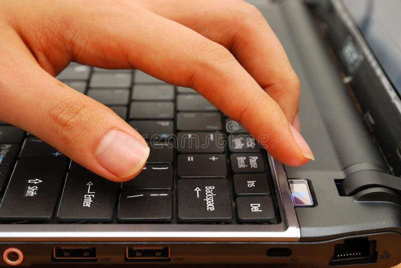 Doigt appuyant sur le bouton de pouvoir sur l'ordinateur portatif image libre de droits