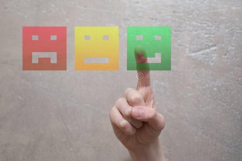 Doigt appuyant sur le bouton heureux vert de visage photos stock
